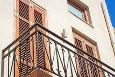 Fragment einer Fassade eines Hauses mit einem Balkon und der Vorhänge von t Stockbilder