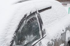 Fragment eines Autos unter einer Schneeschicht während der schweren Schneefälle vor dem Prozess der Schneereinigung lizenzfreie stockfotografie