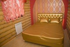 Fragment eines Betts mit weißer Kissen-, nightstand- und Wandlampe Lizenzfreies Stockfoto