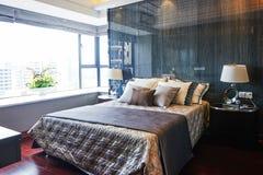 Fragment eines Betts mit weißer Kissen-, nightstand- und Wandlampe Stockbild