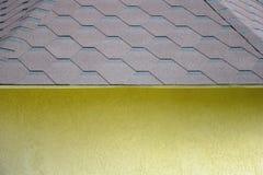Fragment eines gelben kleinen Hauses mit einem Dach bedeckt mit flexiblen Schindeln in Form von Bienenwaben stockbilder