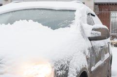 Fragment eines schmutzigen Autos unter einer Schneeschicht während schwere Schneefälle vor dem Schneereinigungsprozeß stockbild