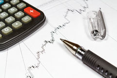 Fragment of electronic calculator and ball pen on the background of currency growth schedule royalty free stock photography