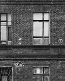 Fragment of the facade of an old brick building. High Windows and textured materials. Black and white. Styling. Architectural background Royalty Free Stock Photo