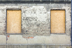 Fragment of facade of an old devastated building. With window holes covered with sheet metal and plywood royalty free stock images