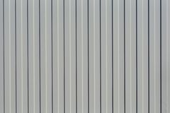 Fragment of a fence from the profiled sheet of gray. Abstract, geometric background. royalty free stock photos