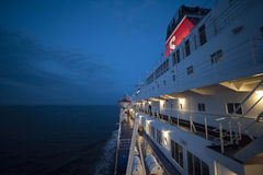 Fragment of a ferry in the sea at night, with illuminated decks Royalty Free Stock Photo