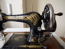 Fragment of first hand SINGER sewing machine, flywheel, selective focus royalty free stock photo