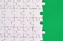 Fragment of a folded white jigsaw puzzle on the background of a green plastic surface. Texture photo with copy space for text.  stock photo
