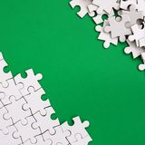 Fragment of a folded white jigsaw puzzle and a pile of uncombed puzzle elements against the background of a green surface. Texture. Photo with space for text Stock Images