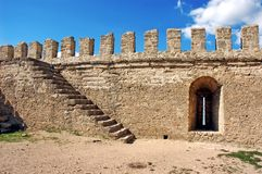Fragment of the fortress wall with stairs and embrasure. Background of stone wall texture photo stock image