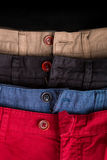 Fragment of four cotton twill pants red, blue, black, beige with open buttons. Close up. Royalty Free Stock Photography