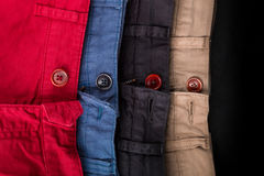 Fragment of four cotton twill pants red, blue, black, beige with open buttons. Close up. Stock Photos