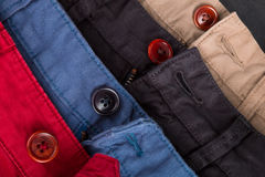 Fragment of four cotton twill pants red, blue, black, beige with open buttons. Close up. Royalty Free Stock Photo