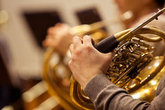 Fragment of a French horn  in the hands of the musician. Hand of a man playing the French horn Stock Images