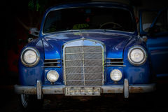 Fragment of the front part of old classic vintage car standing in dark background Stock Image