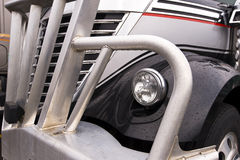 Fragment of the front part of the sem truck. Detail of the front of a modern dark semi truck, including the hood, chrome grille, headlamp, wing with raindrops Royalty Free Stock Images