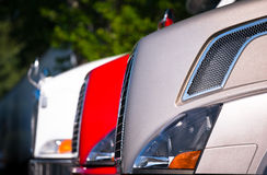 Fragment of front part of semi trucks Standing in row Stock Image