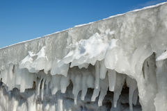 Fragment of a frozen breakwater wall with icicles Stock Photos