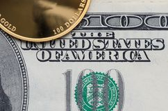 A fragment of gold coin with a face value of 100 dollars and one-hundred-dollar bills.  royalty free stock photo