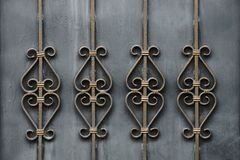 A fragment of gray doors with forged bars and a beautiful pattern Stock Image