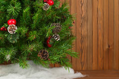 Fragment of Green Decorated Christmas Tree on Wooden Background. Royalty Free Stock Photo