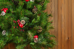 Fragment of Green Decorated Christmas Tree on Wooden Background. Stock Photos