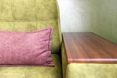 Fragment of a green sofa with a wooden armrest and a pink pillow. Fragment of green, new sofa with wooden armrest and pink pillow Stock Image