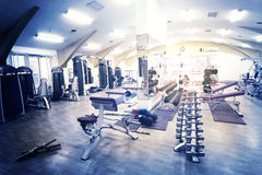 Fragment of gym with exercise equipment. Lit from window Royalty Free Stock Image
