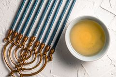 Fragment of Hanukkah with blue candles and butter in a bowl Royalty Free Stock Image