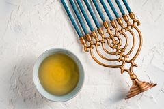 Fragment of Hanukkah with blue candles and butter in a bowl top view Royalty Free Stock Photos
