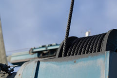 Fragment of heavy duty loading machinery with drum of greasy steel cable. Royalty Free Stock Image