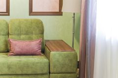 Fragment of the interior with a green sofa and picture cards Stock Photography