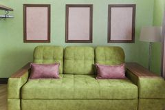 Fragment of the interior with a green sofa and picture cards Royalty Free Stock Photos