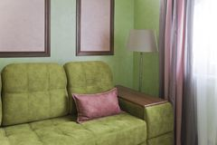 Fragment of the interior with a green sofa and picture cards Royalty Free Stock Image