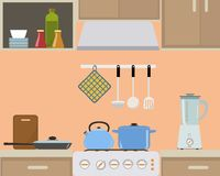 Fragment of an interior of kitchen in orange color. There is a blue kettle and pan on the stove, also blender, a frying pan and other objects in the picture Stock Photo