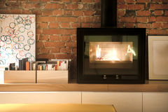 Fragment of interior loft. Burning fireplace. Picture Frames and Stock Image