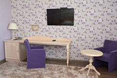 Fragment of an interior of a modern hotel room with upholstered. Furniture and the TV in lilac tones. Drawing room Royalty Free Stock Photo