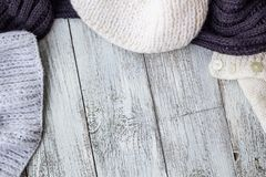 Fragment of knitting clothes on white wooden background.  Royalty Free Stock Photos