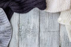 Fragment of knitting clothes on white wooden background.  Stock Image