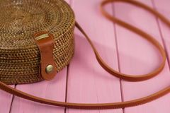 Fragment ladies handbag braided with brown strap on a pink background. Selective focus royalty free stock photos