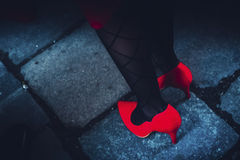 Fragment of lady in red shoes. Fragmental photo of a lady wearing red shoes on pretty legs Royalty Free Stock Photography