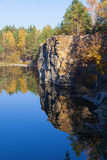 Fragment of the lake shore with stone in autumn forest Royalty Free Stock Image