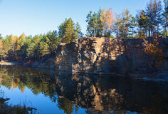 Fragment of the lake shore with stone in autumn forest Stock Images