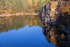 Fragment of the lake shore with stone in autumn forest Stock Photography
