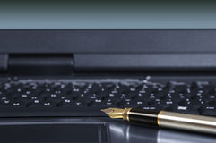 Fragment of laptop with a pen. Pen on the keyboard of the personal computer Royalty Free Stock Photos