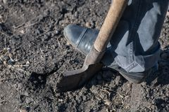 A fragment of a leg of the worker who digs with a shovel empty b stock photography