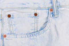 Fragment of light colored artificially aged jeans with reinforcing pocket. Reinforcinged with copper rivets pocket of the new light colored jeans artificially royalty free stock photos