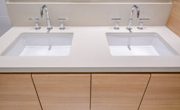 Fragment of luxury bathroom. With double sink and wooden cabinets Stock Photos