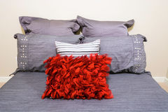 Fragment of a luxury bedroom. Fragment of modern grey bedroom interior with red and silver designer pillows in a luxury house Royalty Free Stock Photos